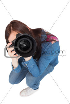 High angle view of casual young photographer taking picture of camera
