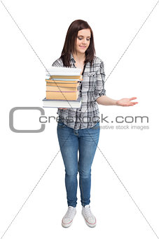 Smiling pretty student holding pile of books