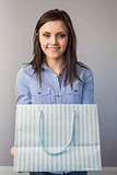 Cheerful pretty brunette offering a present