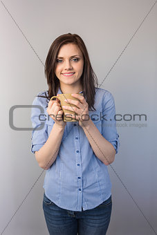 Cheerful pretty brunette holding cup of coffee