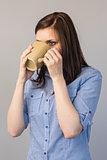 Pensive pretty brunette drinking coffee