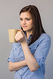 Pensive pretty brunette holding cup of coffee