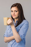 Smiling pretty brunette holding cup of coffee