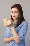 Serious pretty brunette holding cup of coffee