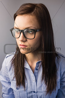 Thoughtful pretty brunette wearing glasses posing