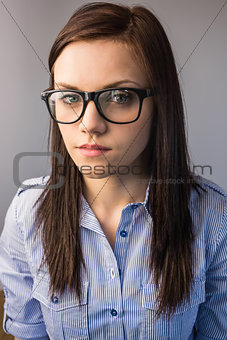 Serious pretty brunette wearing glasses posing
