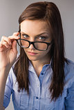 Serious brunette holding glasses posing