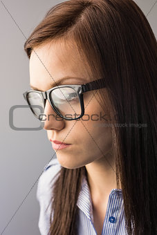 Day dreaming brunette with glasses posing