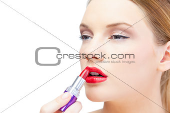 Glamorous blonde model applying red lipstick