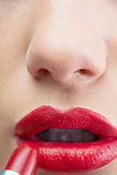 Extreme close up on sensual red lips being made up
