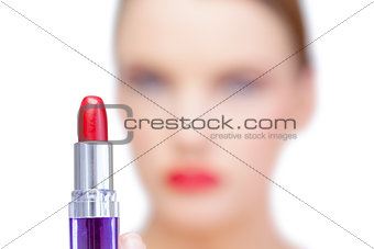 Nude blonde model holding red lipstick