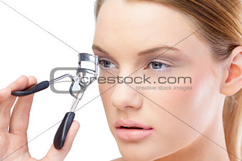 Attractive blonde model using eyelash curler