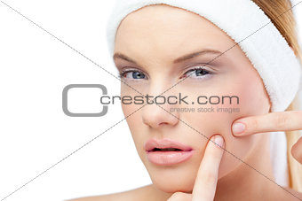 Pretty blonde model pressing pimple on her cheek