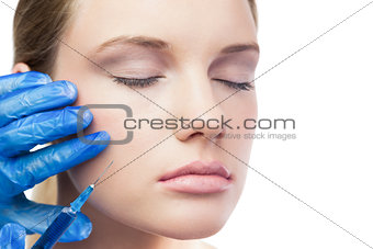 Relaxed cute model having botox injection on the cheek