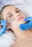 Surgeon making injection above lips on pretty woman lying