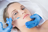 Surgeon making injection above lips on cute woman lying