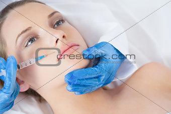 Surgeon making injection above lips on young woman lying