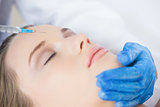Surgeon making injection on forehead on content woman lying