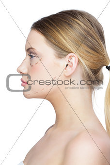 Profile view of calm pretty blonde with dotted lines on the face