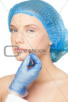 Surgeon drawing dotted lines on content young patient