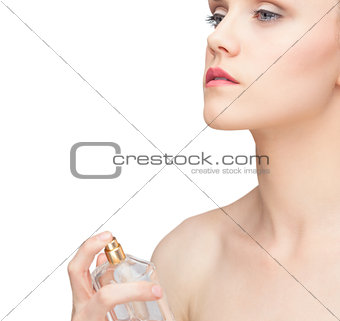 Beautiful nude model spraying perfume