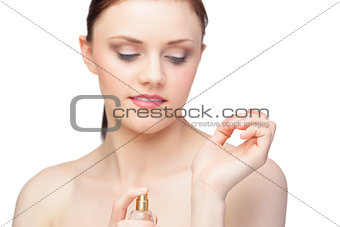 Beautiful nude model spraying perfume on her wrist