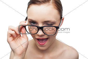 Cheerful model winking at camera over her classy glasses