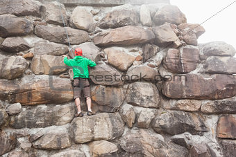 Determined man scaling a large rock face