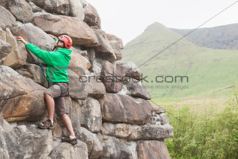 Focused man climbing a large rock face