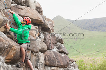 Focused man scaling a large rock face