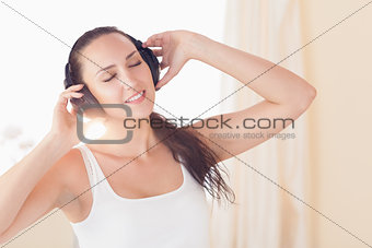 Happy brunette sitting on bed listening to music