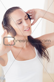 Peaceful brunette sitting on bed listening to music