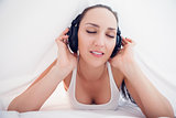 Happy brunette lying under the sheets listening to music