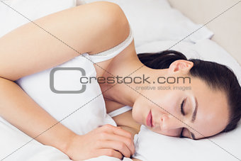 Beautiful brunette lying on her bed asleep