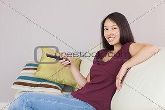 Happy asian girl watching tv smiling at camera