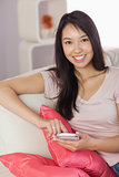 Happy asian girl using her smartphone on the couch looking at camera