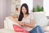 Pretty asian girl using her smartphone on the couch