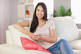 Pretty asian girl using her smartphone on the couch smiling at camera
