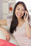 Pretty asian girl talking on her smartphone on the couch