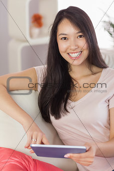 Pretty asian girl using her tablet on the couch smiling at camera