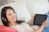 Girl using her tablet pc on the sofa and listening to music smiling at camera