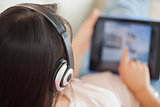 Girl using her tablet on the sofa and listening to music
