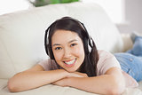 Smiling asian girl lying on the sofa and listening to music