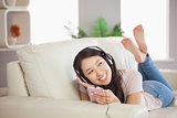 Smiling asian girl lying on the sofa and listening to music with smartphone