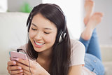 Happy asian girl lying on the sofa and listening to music with smartphone