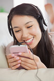 Cheerful asian girl lying on the sofa and listening to music with smartphone