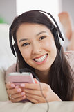 Cheerful asian girl lying on the sofa and listening to music with smartphone looking at camera
