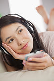 Cheerful asian girl lying on the sofa and listening to music with smartphone looking away