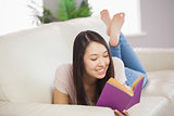 Cheerful asian girl lying on the sofa reading book