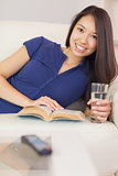Pretty asian girl lying on the sofa reading a novel and drinking water